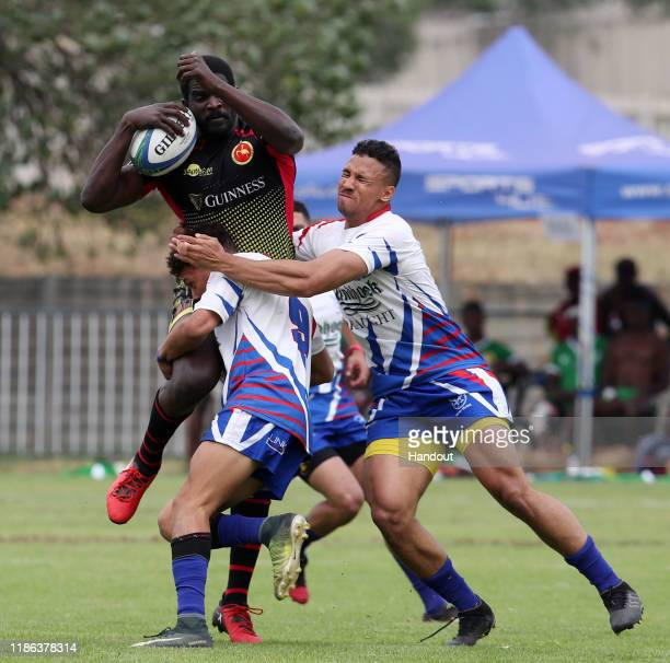Micheal Okorach of Uganda challenged by Adriaan Booysen and Elmarco Beukes of Namibia during the 2019 Rugby Africa Mens 7s match between Namibia and...