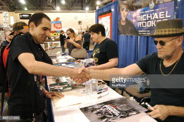 Micheal Rooker shakes the hand of a long time fan o the Walking Dead then signs a poster for him at Wizard World Philadelphia on June 2 2017