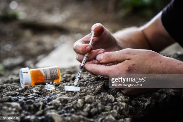 Micheal Rouwhorst prepares a shot of heroin and cocaine near the train tracks along E Tusculum St on Thursday July 27 in Philadelphia PA
