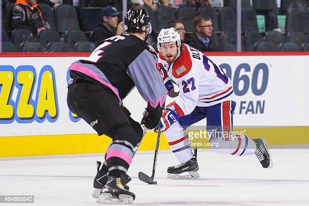 Micheal Zipp of the Calgary Hitmen defends against Kolten Olynek of the Spokane Chiefs during a WHL game at Scotiabank Saddledome on October 29, 2015...
