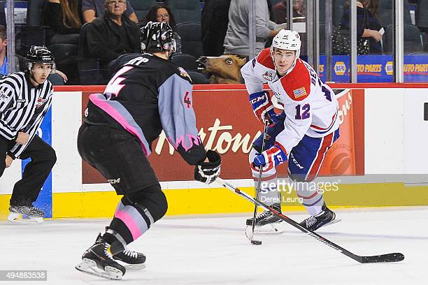 Micheal Zipp of the Calgary Hitmen defends against Markson Bechtold of the Spokane Chiefs during a WHL game at Scotiabank Saddledome on October 29,...