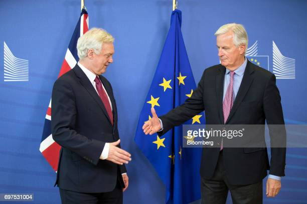 Michel Barnier chief negotiator for the European Union right shakes hands with David Davis UK exiting the European Union secretary ahead of the start...