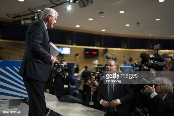 Michel Barnier chief negotiator for the European Union walks off stage while holding the draft withdrawal agreement after a news conference in...