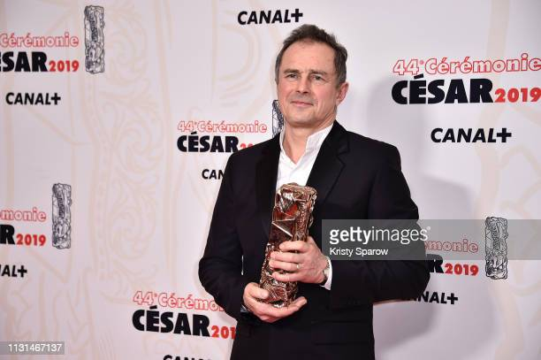 Michel Barthelemy poses with the Cesar award for Best Set Design Award for the film Les Freres Sisters during at Salle Pleyel on February 22 2019 in...