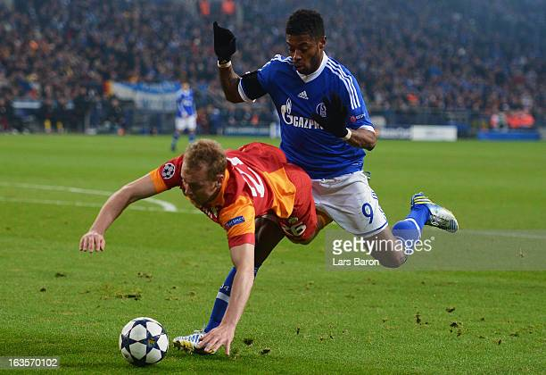 Michel Bastos of Schalke challenges Semih Kaya of Galatasaray during the UEFA Champions League round of 16 second leg match between FC Schalke 04 and...