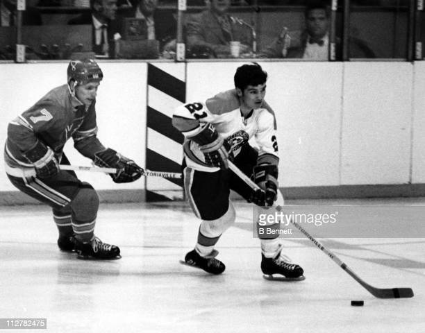 Michel Briere of the Pittsburgh Penguins skates with the puck as he is followed by Red Berenson of the St Louis Blues circa 1969 at the St Louis...