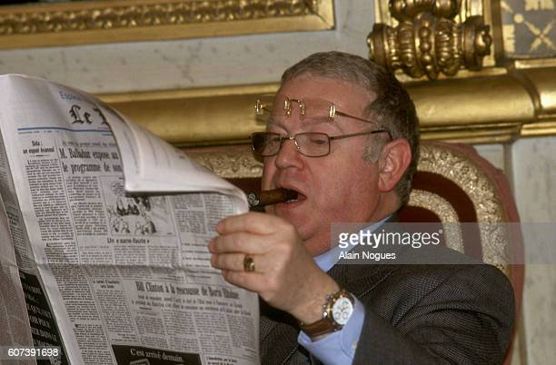 Michel Charasse councilor to President Francois Mitterrand reads a newspaper and smokes a cigar at the reopening of the French Senate