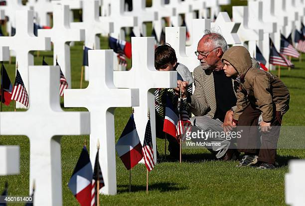 Michel Colas shows his grandsons Samuel Colas and Rafael Schneider the Normandy American Cemetery before the start of an official event with US...