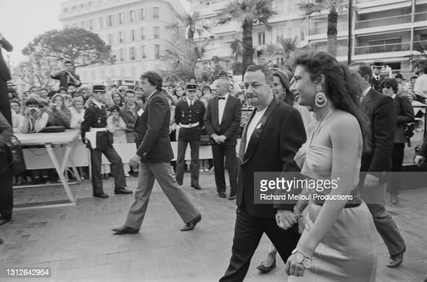 """Michel Colucci alias Coluche et sa compagne Fred Romano au 38ème Festival de Cannes pour la présentation du film de Dino Risi """"Le Fou de Guerre""""."""