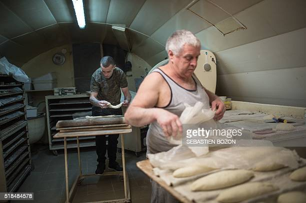 Michel Flamant and Jerome work in their bakery on March 23 in Dole, eastern France. Michel Flamant, the owner of the bakery decided to teach baking...