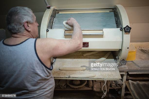 Michel Flamant works in his bakery on March 23 in Dole, eastern France. Michel Flamant, the owner of the bakery decided to teach baking and pastry to...