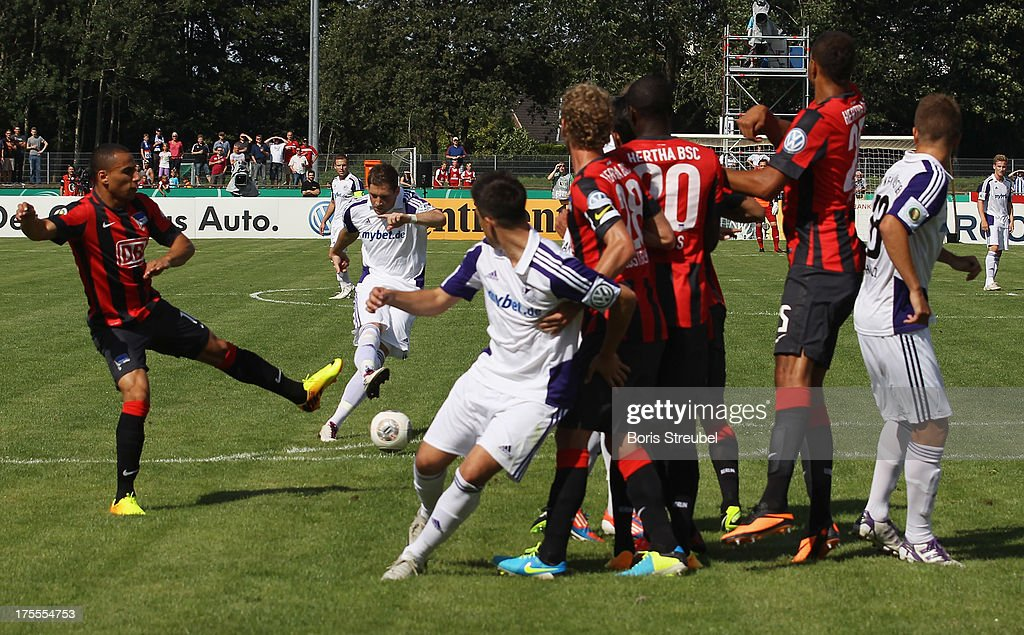 Michel Harrer (2ndL) of Neumuenster scores his team's first goal with a free-kick during the DFB Cup first round match between VfR Neumuenster and Hertha BSC Berlin at Gruemmi-Arena on August 4, 2013 in Neumuenster, Germany.