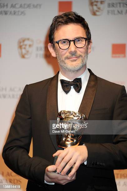 Michel Hazanavicius accepting the Best Cinematography Award on behalf of Guillaume Schiffman poses in the press room at the Orange British Academy...