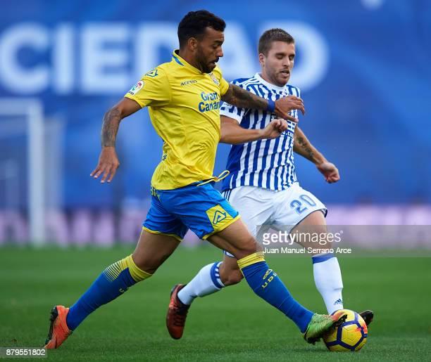 Michel Macedo Rocha of UD Las Palmas duels for the ball with Kevin Rodrigues of Real Sociedad during the La Liga match between Real Sociedad de...