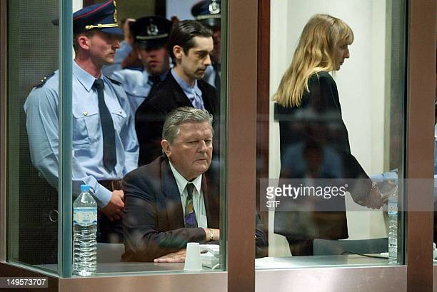 Michel Nihoul sits 17 June 2004 during the reading of the verdict at the Arlon courthouse as coaccused Michel Lelievre and Michelle Martin leave the...