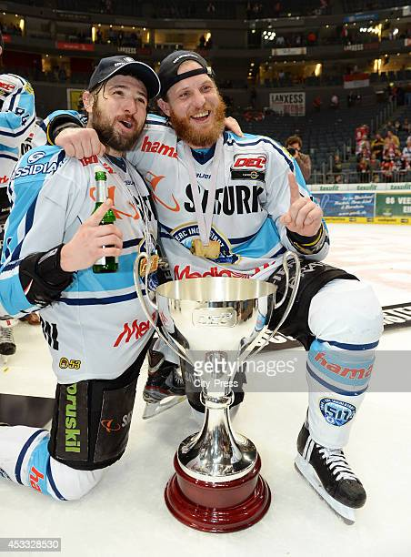 Michel Periard and Timothy Conboy celebrate the championship with the trophy after game seven of the DEL playoff final on April 29, 2014 in Cologne,...