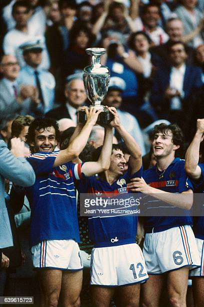Michel Platini , captain of the French soccer team, holds the European Cup trophy with team-mates Alain Giresse and Luis Fernandez after their team...