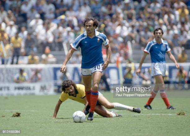 Michel Platini of France moves away from Socrates of Brazil during the FIFA World Cup quarter final between France and Brazil at the Estadio Jalisco...