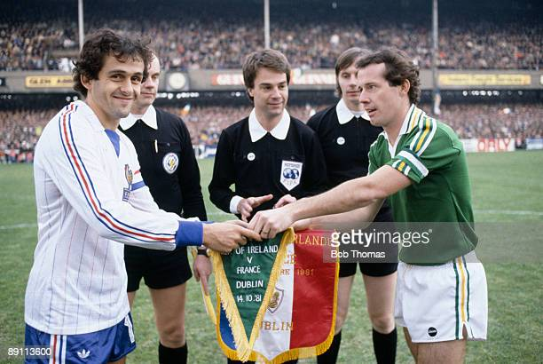 Michel Platini the captain of France exchanges pennants with the Republic of Ireland captain Liam Brady watched by the match officials prior to the...