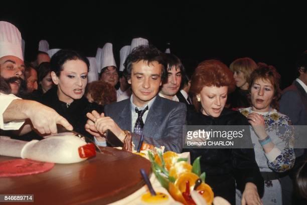 Michel Sardou apres la premiere de son spectacle au Palais des Congres entrain de decouper un enorme gateau entoure de Barbara Serge Lama Regine et...