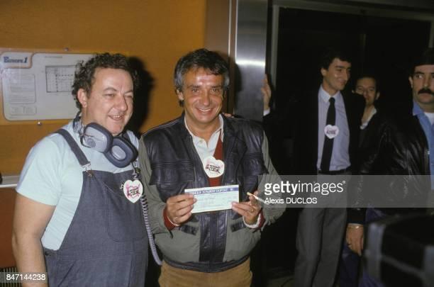 Michel Sardou remet un cheque aux Restaurants du Coeur en presence de Coluche le 14 decembre 1985 a Paris France