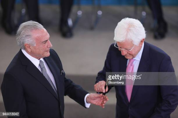 Michel Temer Brazil's president left hands a pen to Wellington Moreira Franco Brazil's mines and energy minister during a swearing in ceremony at the...