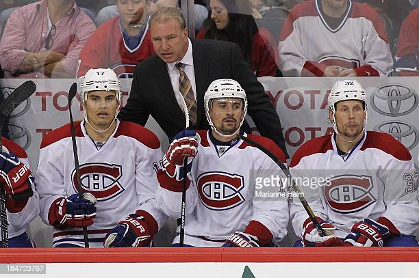 Michel Therrien head coach of the Montreal Canadiens talks to players Rene Bourque Tomas Plekanec and Travis Moen on the bench in third period action...