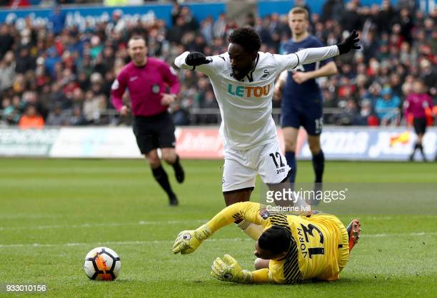 Michel Vorm of Tottenham Hotspur tackles Nathan Dyer of Swansea City during The Emirates FA Cup Quarter Final match between Swansea City and...