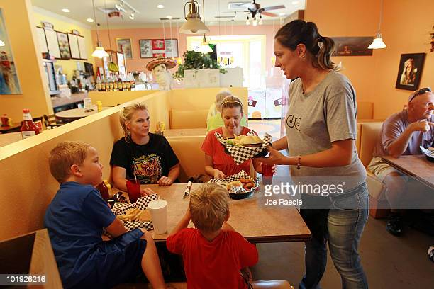 Michela Stievano brings a lunch order to Kerri Turner and Sara Wallace at The Boardwalk Cafe on June 9 2010 in Pensacola Florida The cafe has...