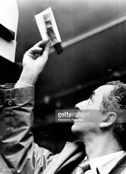 Michelangelo Antonioni Italian film director looking at negatives in a darkroom