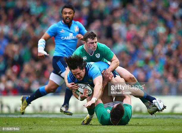 Michele Campagnaro of Italy is tackled by Robbie Henshaw and Jared Payne of Ireland during the RBS Six Nations match between Ireland and Italy at...