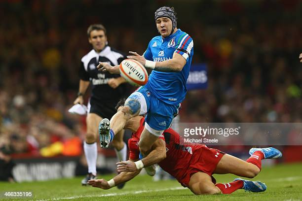 Michele Campagnaro of Italy kicks ahead as Mike Phillips of Wales tackles during the RBS Six Nations match between Wales and Italy at the Millenium...
