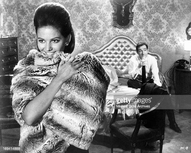 Michele Girardon wrap fur around her with Ugo Tognazzi drinking in the background in a scene from the film 'The Magnificent Cuckold' 1964