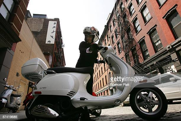 Michele Joerg parks her Vespa scooter April 25 2006 outside of Vespa of SOHO in New York City With fuel prices continuing to rise scooters and other...