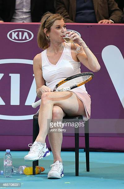 Michele Laroque sips a cup of champagne on the court during the Amelie Mauresmo Tennis Night to benefit the 'Institut Curie' to fight cancer during...