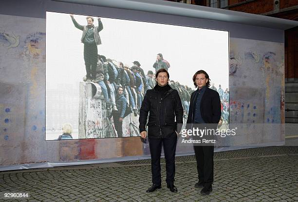 Michele Malenotti and Manuele Malenotti Vice presidents of Belstaff pose in front of a video display that shows images from the former Berlin wall at...