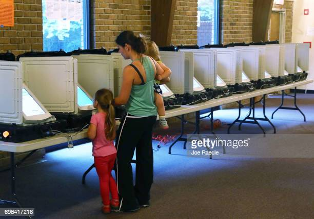 Michele Parsons casts her ballot with her children Maria Parsons and Maya Parsons during a special election in Georgia's 6th Congressional District...
