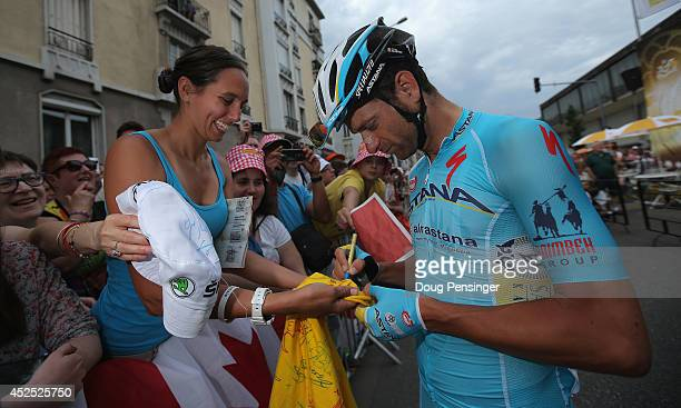 Michele Scarponi of Italy and the Astana Pro Team signs an autograph for a fan at the start of the fourteenth stage of the 2014 Tour de France a...