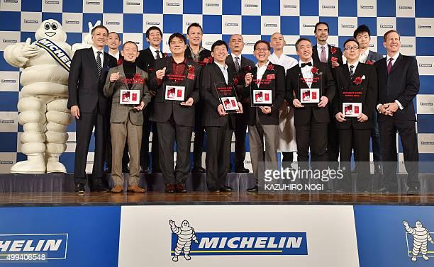 Michelin Japan president Bernard Delmas Michelin guide International Director Michael Ellis and Michelin mascot Bibendum pose with heads of threestar...