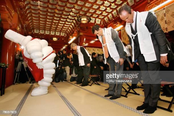 Michelin mascot Bibendum director of the Michelin Guides JeanLuc Naret Michelin Japan president Bernard Delmas and other employees of Michelin Tire...