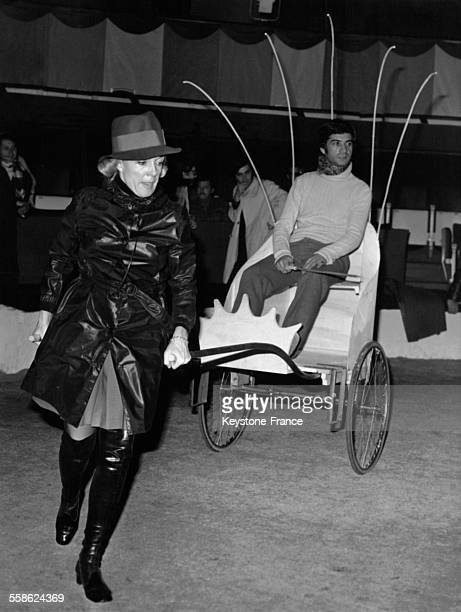 Micheline Presle emmenant JeanClaude Brialy en poussepousse lors des répétitions pour le gala de l'Union des artistes à Paris France le 22 avril 1969