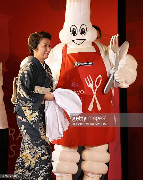 Michelin's new threestarhonoured Tokyo restaurant owner Keiko Mita of Hamadaya is led by Michelin mascot on the stage during a party to commemorate...