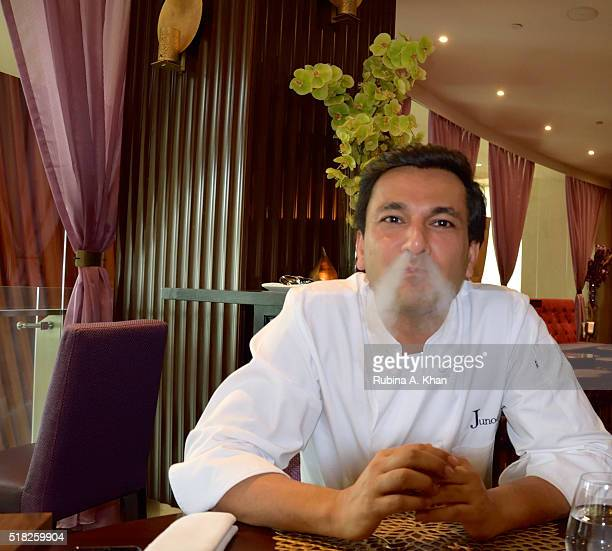 Michelinstarred Indian chef Vikas Khanna enjoys a Table Side Kulfi prepared with liquid nitrogen at his restaurant Junoon on March 30 2016 in Dubai...