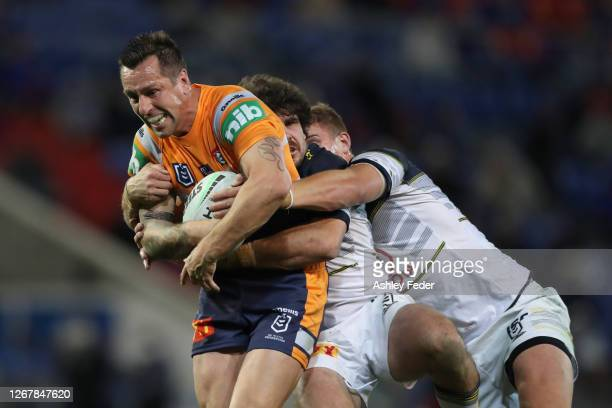 Michell Pearce of the Newcastle Knights is tackled during the round 15 NRL match between the Newcastle Knights and the North Queensland Cowboys at...
