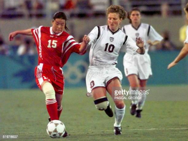 Michelle Akers of the US and China's Guihong Shi fight for the ball during women's Olympic final soccer match late 01 August in Athens ==FOR...