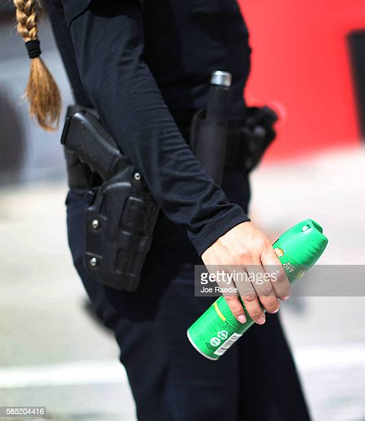 Michelle Albelo A City of Miami police officer gives out cans of insect repellent to help people near the Miami Rescue Mission prevent mosquito bites...