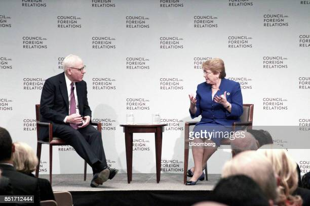 Michelle Bachelet Chile's president right speaks while David Rubenstein cochief executive officer of Carlyle Group LP listens during an event at the...