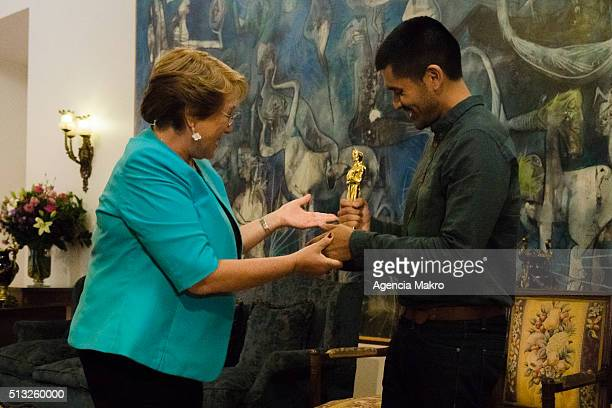 Michelle Bachelet President of Chile takes a look to the Oscar Award holded by director and member of PunkRobot Gabriel Osorio during a meeting at...