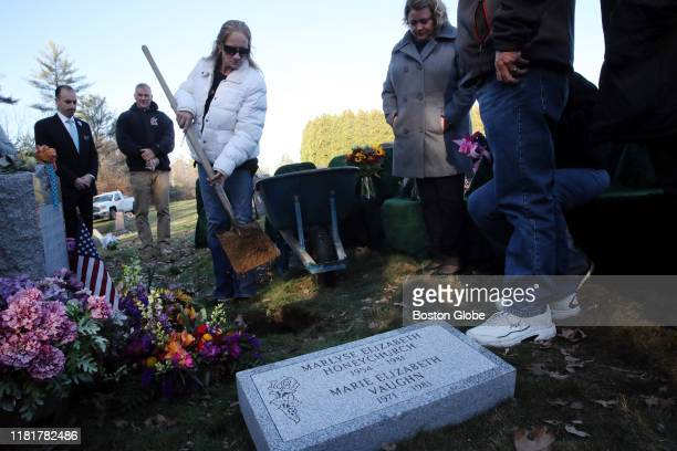 Michelle Chagaris front left is joined by Diane Kloepfer as she places dirt in the grave during a funeral service for Chagaris' sister Marlyse...