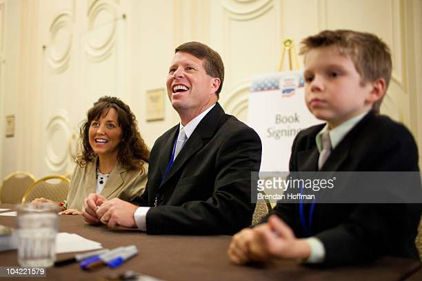 """Michelle Duggar and Jim Bob Duggar, stars of The Learning Channel TV show """"19 Kids and Counting,"""" pose for a picture with a fan while signing copies..."""